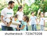 young volunteers and children... | Shutterstock . vector #723675208