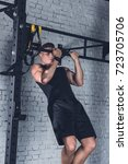 Small photo of young athletic man in sportswear doing pull ups on pull up bar in gym