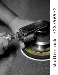 Small photo of Man connecting air hose to orbital sander with selective color