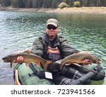 Small photo of Man fly fishing from a pontoon or float tube with his catch, two large trout fish (Brook Trout hybrid with Lake Trout, called Splake)