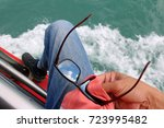 Small photo of Men used a shirttail cleaning the sunglasses on the tour boats with the reflection of the sky.
