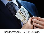 Small photo of Concept for corruption, finance profit, bail, crime, bribing, fraud, auction bidding Bundle of dollar cash in hand