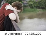 teen boy leaning over a bridge... | Shutterstock . vector #724251202