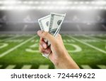 Small photo of Close up of a man's hand crushing a wad of hundred dollar bills in concept of getting money with bets in American football