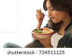 woman eating a healthy bowl of... | Shutterstock . vector #724511125