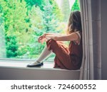 a young woman is sitting by the ... | Shutterstock . vector #724600552