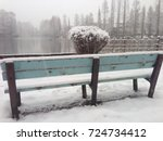 A Snow Covered Bench Facing...