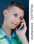 Small photo of Portrait of a young boy . Pimples on the face , the transition to adulthood . A guy with a riot of hormones . teenager on the phone