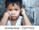 Stock photo poverty portrait of a cute young asian boy filipino male against wall with copyspace 72477415