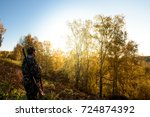 Small photo of A hunter with a gun in the forest at dawn.