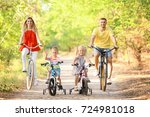 happy family riding bicycles in ... | Shutterstock . vector #724981018