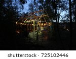 Small photo of A selfmade phantasy play house in a garden iluminated at dawn.