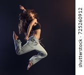 Stock photo young athletic slim dancer performing and jumping on dark background fitness and vitality concept 725260912