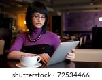 girl in cafe uses small mobile computer - stock photo