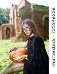 Small photo of Gloomy halloween girl in black warlock holding jack-o-lantern
