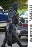 Small photo of A SWAT officer takes his gear closer to the scene of a hostage negotiation.