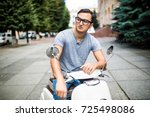 young man riding a vintage... | Shutterstock . vector #725498086