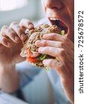 hungry man eats a big sandwich | Shutterstock . vector #725678572