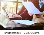 Small photo of Two businesswoman working together about documents and us laptop , partner discuss plan or idea and opinion meeting, Asian bussiness are discussing their working beside window at coffee shop
