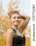 Small photo of Girl in leather accoutrements on a background of yellow autumn foliage