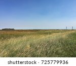 Railway Track and Meadow on Canadian Prairie Under Blue Sky - stock photo