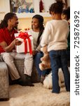 Small photo of Afro-American family with gift for Christmas at decorated home