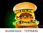 Tasty and appetizing hamburger on a darkly green background - stock photo