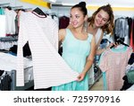 glad young women shopping at... | Shutterstock . vector #725970916