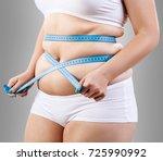 overweight woman measuring her... | Shutterstock . vector #725990992