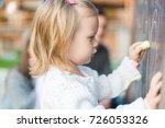 cute little girl drawing on... | Shutterstock . vector #726053326