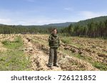 Small photo of Finding a position using a gps device in an outdoor field. Forest warden on the hillside looking in the navigation GPS in the background a field of a forest nursery with plantings of pine and cedar.