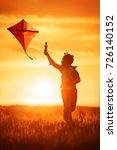 boy launch a kite in the field... | Shutterstock . vector #726140152