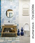 Small photo of Modern spacious bathroom with bright tiles with toilet and sink. Side view