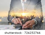 Small photo of Double exposure of businessman working with calculator, cityscape and urban at sunset with node of networking as business, worker, technology, communication and Calculation concept