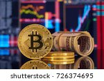 Small photo of Golden bitcoin are stacked on a bright background of business graphs close-up. Bitcoin cryptocurrency. Folded in a tube 100 dollar bills