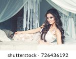 Small photo of Beautiful Alluring Brunette Woman in White Lingerie Dress on the Bed on Vintage Interior