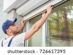 man measuring window prior to... | Shutterstock . vector #726617395
