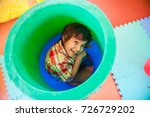 boy hiding in a plastic barrel | Shutterstock . vector #726729202