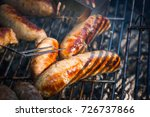 Small photo of Mixed variety of mouthwatering char grilled sausages on barbecue grill outdoor in garden, view from above, close-up