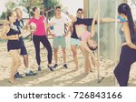 Small photo of Sporty girl performing pole exercises causing admiration of people watching her