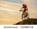 Small photo of Cyclist in Red T-Shirt Riding the Bike Down the Rock on the Sunset Sky Background. Extreme Sport and Enduro Biking Concept.