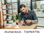 focused young man reading...   Shutterstock . vector #726964756