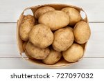 raw potato and basket on wooden ... | Shutterstock . vector #727097032