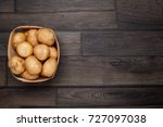 raw potato and basket on wooden ... | Shutterstock . vector #727097038