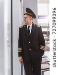 Small photo of Cheerful smiling adult airman glancing though window
