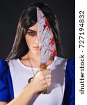 Small photo of Portrait of a young woman with knife dressed as Alice in Wonderland, video game.