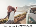 Female friends on road trip enjoying outdoors on a sunny day. Women standing outside van  and laughing. - stock photo