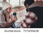 Couple of friends on roadtrip sitting at the back in their camper van. Smiling woman holding coffee and man looking at the map. - stock photo
