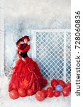 Small photo of Fashionable woman in red lavish dress posing under falling snow.