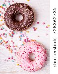Small photo of Overtop view of donuts in and sweet candy on white wooden background. Delicious junk food